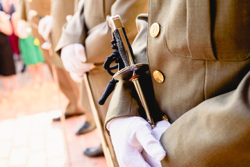Army soldiers with gloves holding their sabers waiting to be checked by the superior