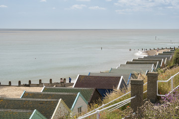 A row of beach hut roofs with the sea beyond