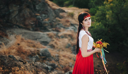 Beautiful woman with a bouquet of wild flowers on the background of the nature of the island of Khortytsya. The modern Ukrainian patriot.