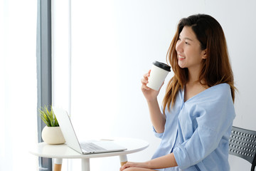 Young asian woman holding a coffee cup with smiling face, positive emotion at working desk background, casual office life, working from home concept