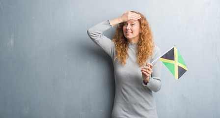 Young redhead woman over grey grunge wall holding flag of Jamaica stressed with hand on head, shocked with shame and surprise face, angry and frustrated. Fear and upset for mistake.