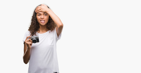 Young hispanic woman taking pictures using vintage camera stressed with hand on head, shocked with shame and surprise face, angry and frustrated. Fear and upset for mistake.