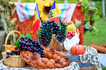 Moldova Independence Day celebrated on August 27. Elements of the Moldovan national identity: tricolor flag, grape vines, grapevine, wine barrel and baked bread (colacul). Conceptual picture.
