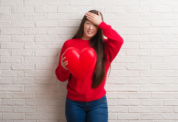 Young Chinese woman in love over brick wall holding red heart stressed with hand on head, shocked with shame and surprise face, angry and frustrated. Fear and upset for mistake.