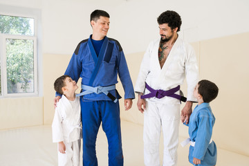 Male karate instructors training little children boys in dojo or jiu-jitsu at gym at tatami. Trainer teaches kid the basics of fighting for self-defense. Group of man and kids in sambo training