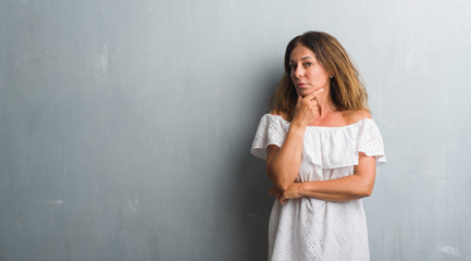Middle age hispanic woman standing over grey grunge wall looking confident at the camera with smile with crossed arms and hand raised on chin. Thinking positive.