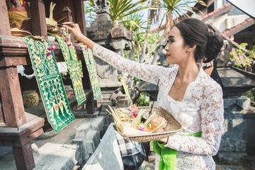 balinese woman doing ritual offering canang sari and praying at