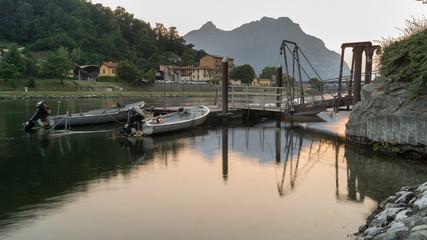 barche al tramonto, ormeggiate al pontile lungo il fiume