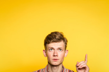 look up. funny comic man pointing upward with a hand. portrait of a young guy on yellow background popping up or peeking out from the bottom. free space for advertisement.
