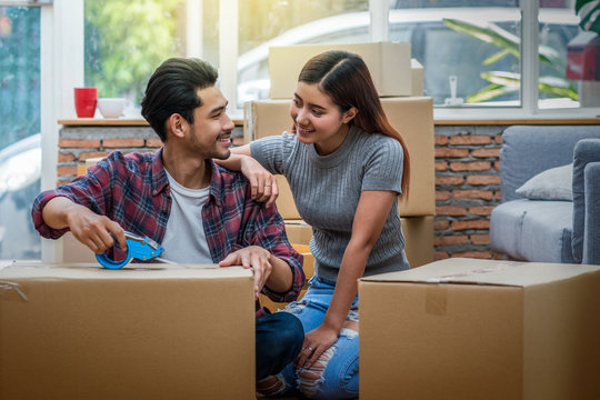 Asian young couple packing the big cardboard box for moving in new house, Moving and House Hunting concept,