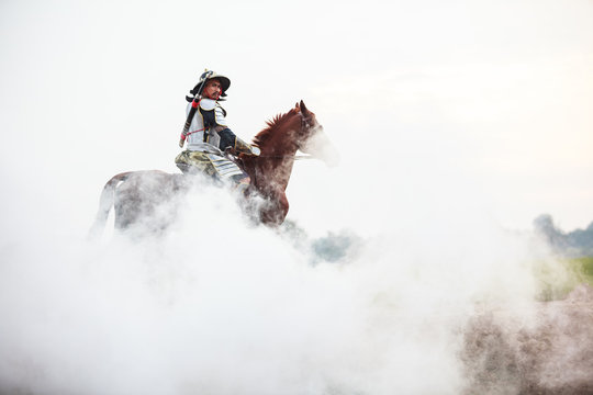 Asian Thai Warrior in traditional armor suit riding horse in white fog with rural farm background. Vintage Retro war costume concept.