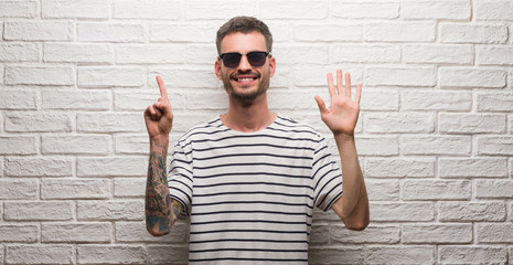 Young adult man wearing sunglasses standing over white brick wall showing and pointing up with fingers number six while smiling confident and happy.