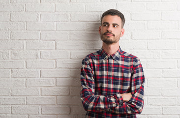 Young adult man standing over white brick wall smiling looking side and staring away thinking.