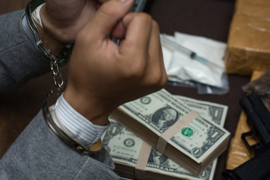 Businessmen arrested, man with handcuffs  with money and drug.