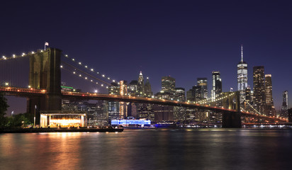 Panorama of Brooklyn Bridge and New York City (Lower Manhattan) with lights and reflections at dusk, USA