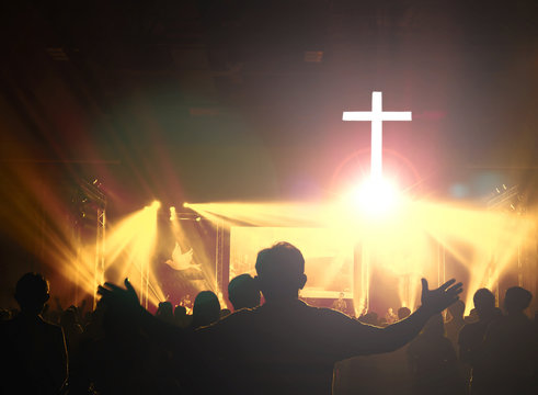 Church worship concept:Christians raising their hands in praise and worship at a night music concert