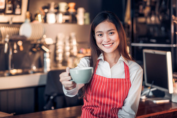 asian woman barista wear red apron holding hot coffee cup and smiling at bar counter with happy emotion,Cafe restaurant service concept,selective focus on smiling face.
