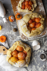 The process of cooking apricot pie. Fruits in a dough, flour. Flat lay. Working conditions in the kitchen. Galette