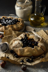 Pies with black currant on kraft paper. Galette. Gray background
