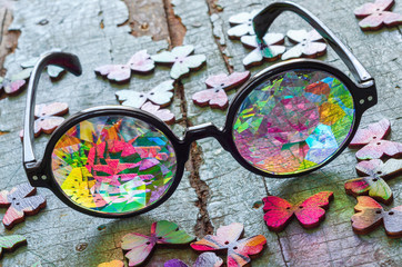 designer kaleidoscope glasses on a blue wooden background with butterflies