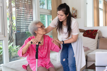 Young carer supporting senior disabled woman with walking stick