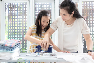 Happy family mother and daughter together engaged in housework iron clothes iron at home