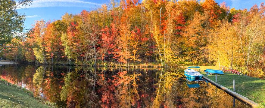 Lake, boat and trees in foliage season, panoramic view