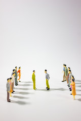 Two team of miniature business people confront on white background.