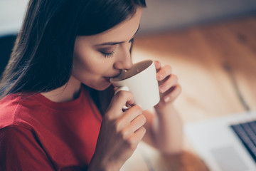 Crop photo of a girl who enjoys delicious aroma coffee with from a white mug sitting in a cafe