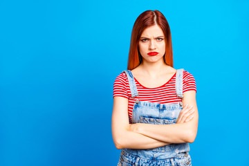 Red straight-haired vivid young girl with folded hands, wearing casual, isolated over blue background, copy space