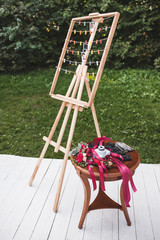 Decorated wooden table and hanger for polaroid photos for guests in wedding reception