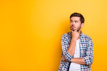Close up portrait of thoughtful man who looks away touching his chin and weighs the pluses and minuses of the offer isolated on bright yellow background with copy space for text Wall mural