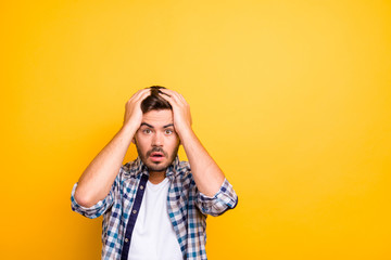 Portrait of frightened brunette man in a plaid shirt holds his hands behind his head and looks into the camera isolated on shine yellow background with copy space for text