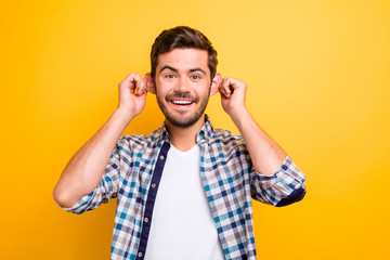 Portrait of attractive funny man stretching ears imitating monkey and looking at camera isolated on vivid yellow background
