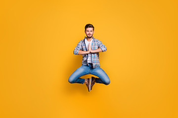 Full-body portrait of levitates in the air meditating and concentrating isolated on shine yellow background