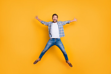 Full-legh portrait of of crazy and excited handsome man jumping up like a star isolated on shine yellow background