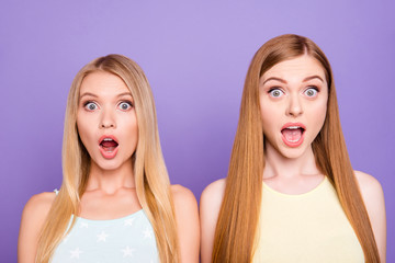 Head shot portrait of shocked astonished girls with long hair keeping eyes and mouth wide open looking at camera isolated on vivid violet background