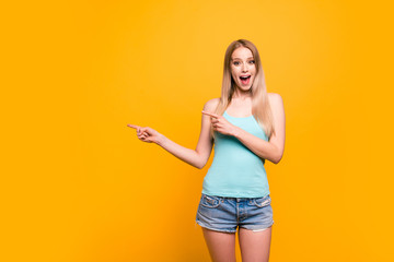 Attractive cute straight-haired blonde caucasian smiling girl, wearing casual blue shirt and jeans shorts, amazed, pointing showing with two fingers to object. Isolated over yellow background