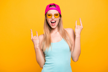 Attractive cute straight-haired blonde caucasian funny girl, wearing casual blue shirt and vivid bright pink cap, showing double horns sign with hands. Isolated over yellow background