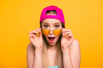 Summer discounts for travel! Close up portrait of shocked and surprised girl looks at the camera over glasses with wide-open eyes and mouth isolated on shine yellow background.