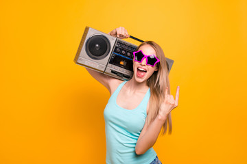 Stylish and young fashion blonde giving the Rock and Roll sign and holds a tape recorder on her shoulder isolated on vivid yellow background
