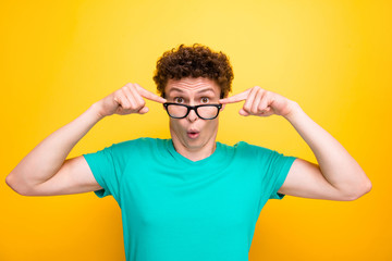 Handsome curly-haired shocked young guy wearing casual green t-shirt, showing surprised gesture, putting glasses down. Isolated over yellow background