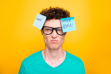 Handsome curly-haired upset young guy wearing casual green t-shirt and glasses. Two stickers with texts pinned on head. Isolated over yellow background