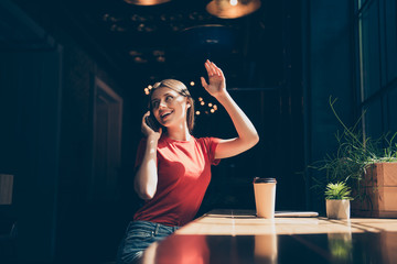 Attractive nice smiling young girl wearing casual sitting in cafeteria, talking on phone, waving, waiting for friend, drinking coffee, dark interior
