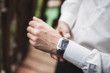 Man in white shirt wearing classic silver watches. Getting ready for wedding