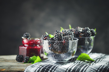 Ripe blackberry and blackberry jam on a wooden table. Dark background.