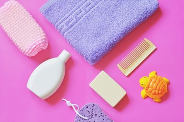 Flat lay baby bath products/ Purple sponge, shampoo, rubber turtle toy, soap bar and wooden comb on a pink background