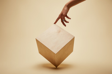 cropped image of woman touching wooden cube on beige