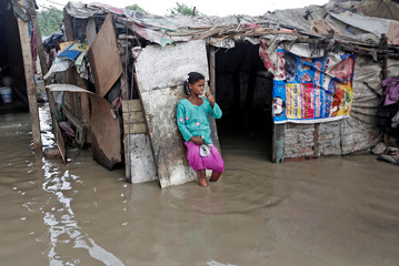 A girl brushes her teeth as she stands outside her submerged shanty at a slum area after a rise in the waters of the river Yamuna in New Delhi