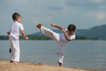 Training of two children on the beach: capoeira, sports
